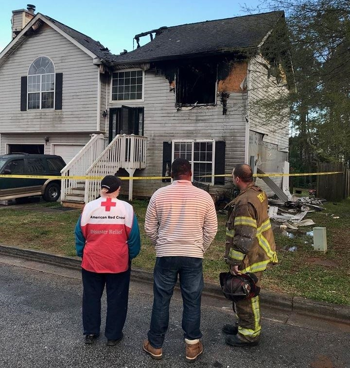 A representative from the Red Cross, a man and a firefighter stand in front of a house damaged by fire.