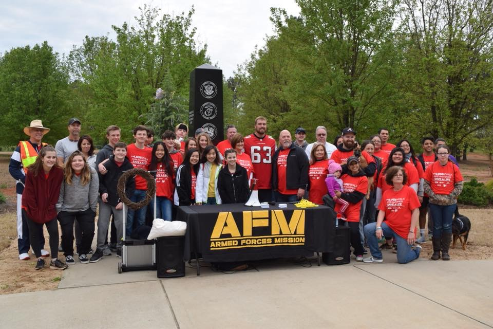 A large group of people wearing red shirts stand in front of an Armed Services Mission table.