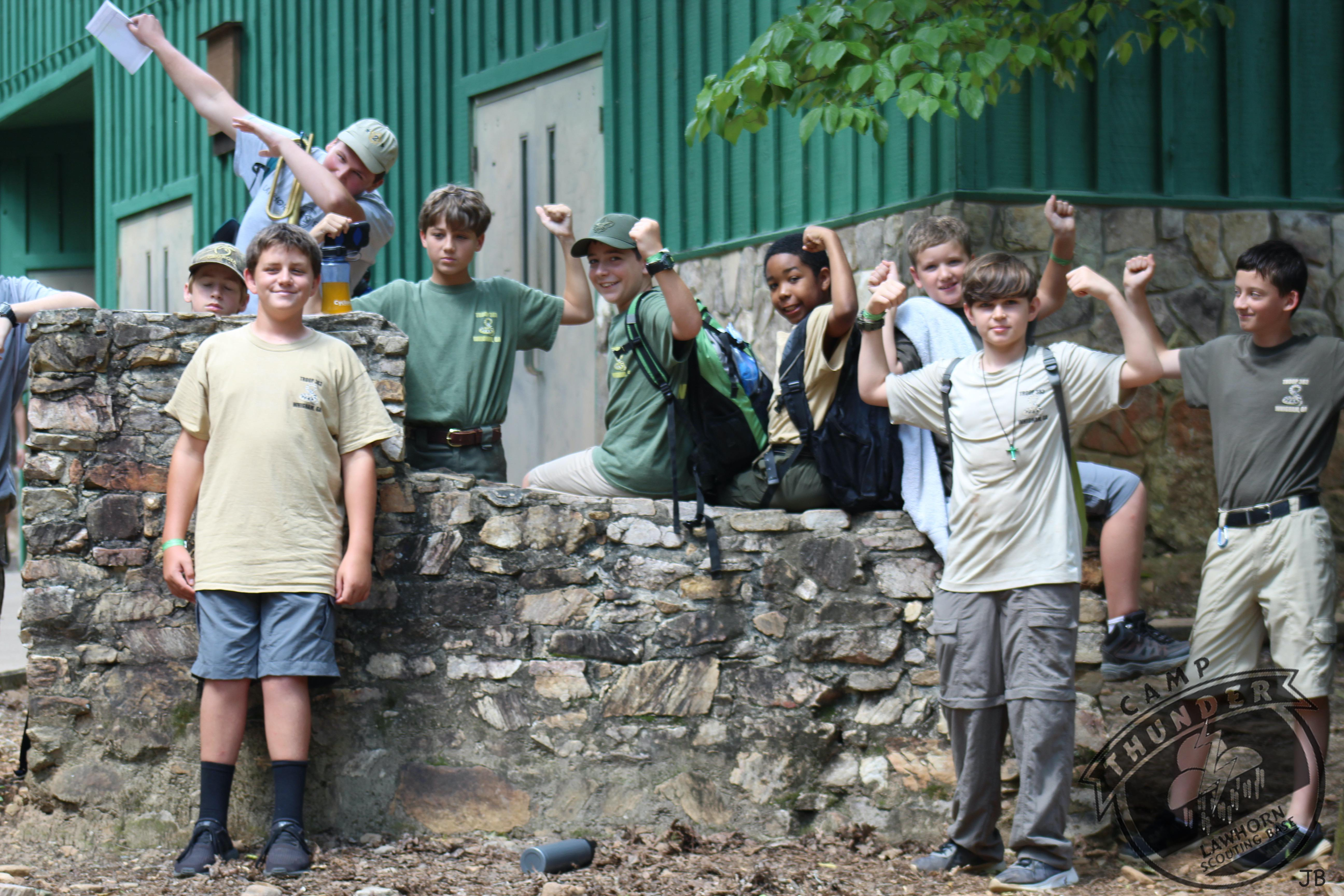 Nine Boy Scouts pose in front of a stone wall.