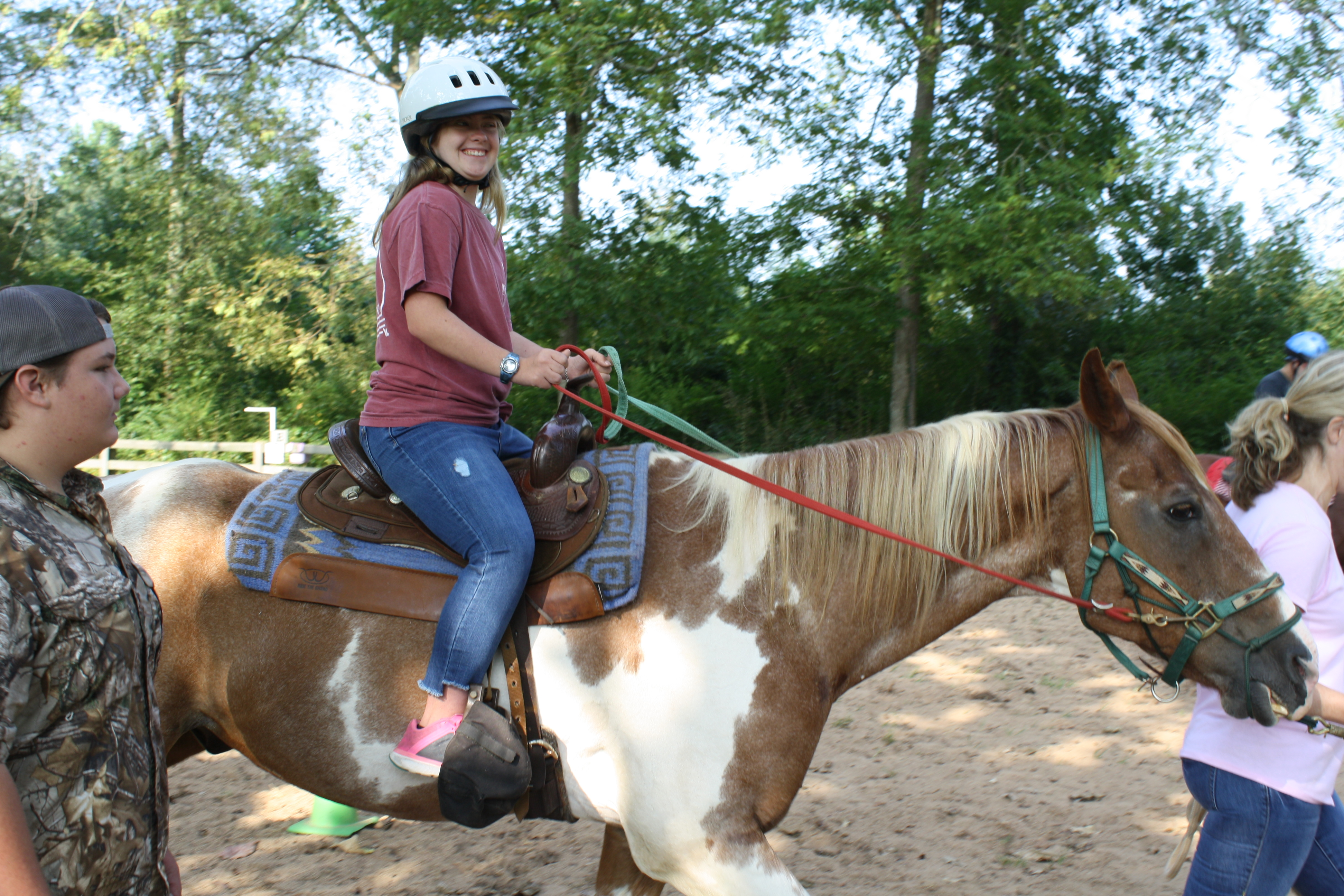 A smiling girl rides a horse.