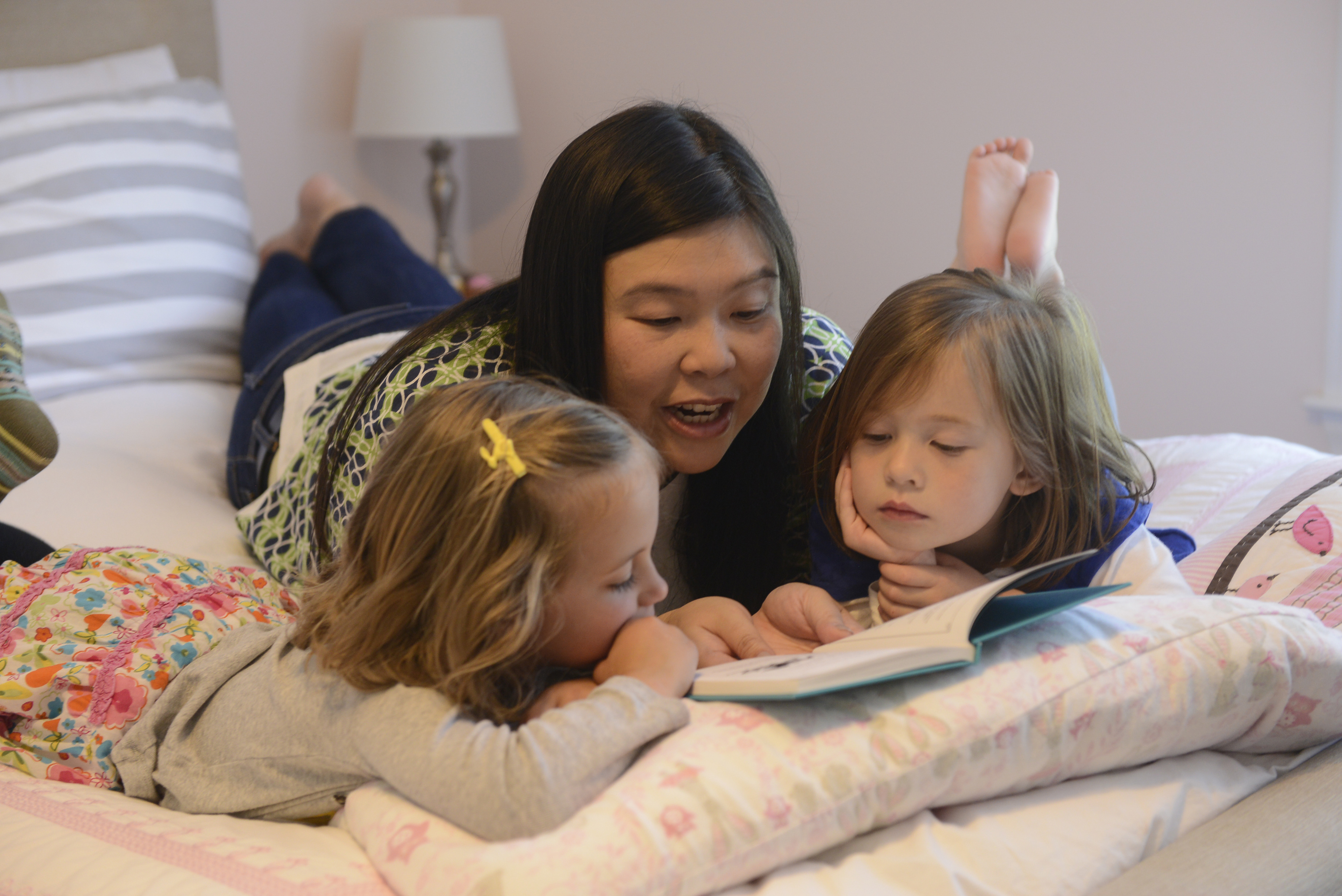 A woman reads to two girls on a bed.