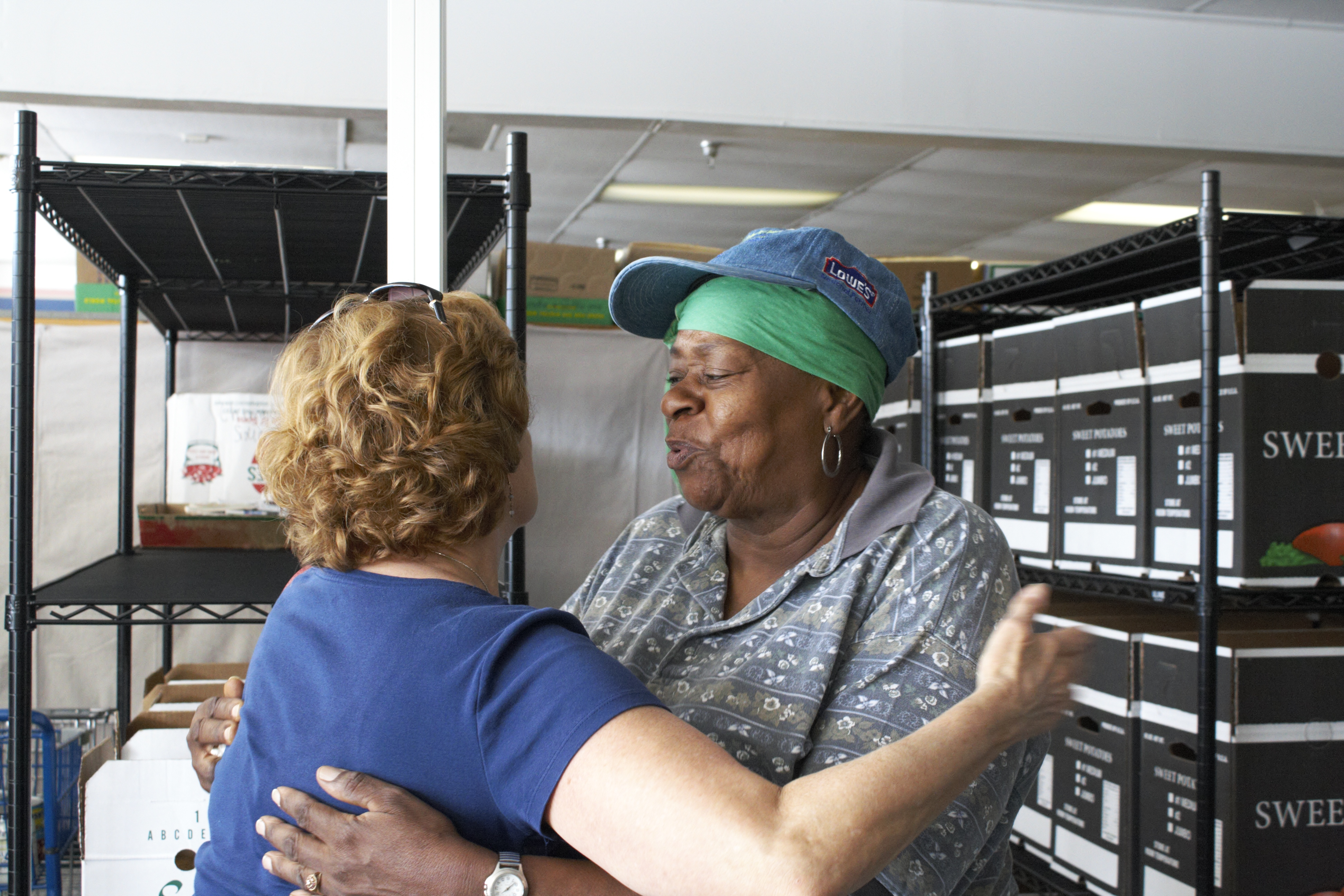 One woman hugs another woman in front of food pantry shelves..